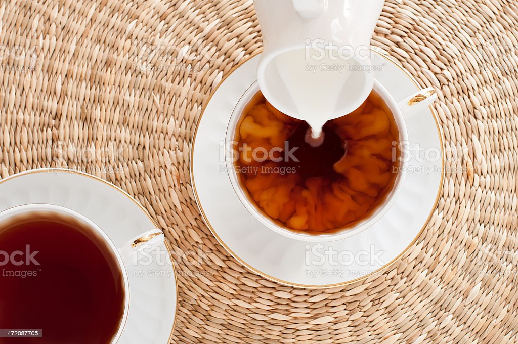 Milk pouring into cup of tea stock photo