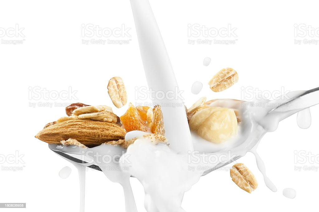 Milk pouring over spoonful of fruit and nut muesli stock photo