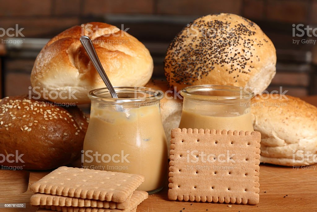 Milk pudding dessert in jar with bread rolls and cookies stock photo