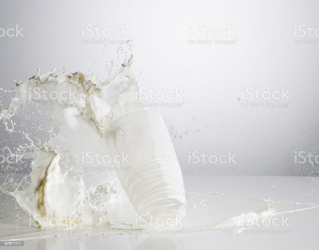 Milk spilling from glass stock photo