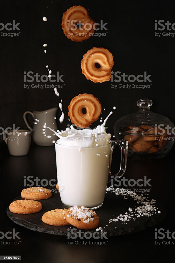 Milk splash. Falling cookies to glass of milk with splash on black background. stock photo