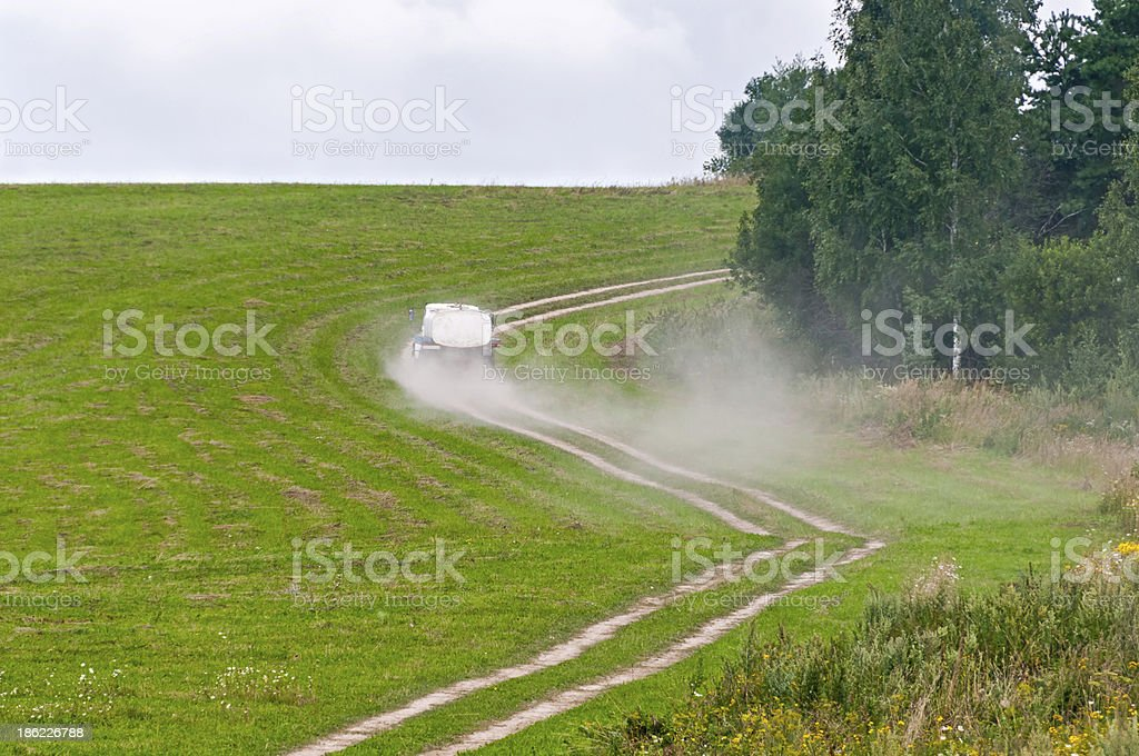 Milk tanker rises in dust puff on zigzag dirty road stock photo