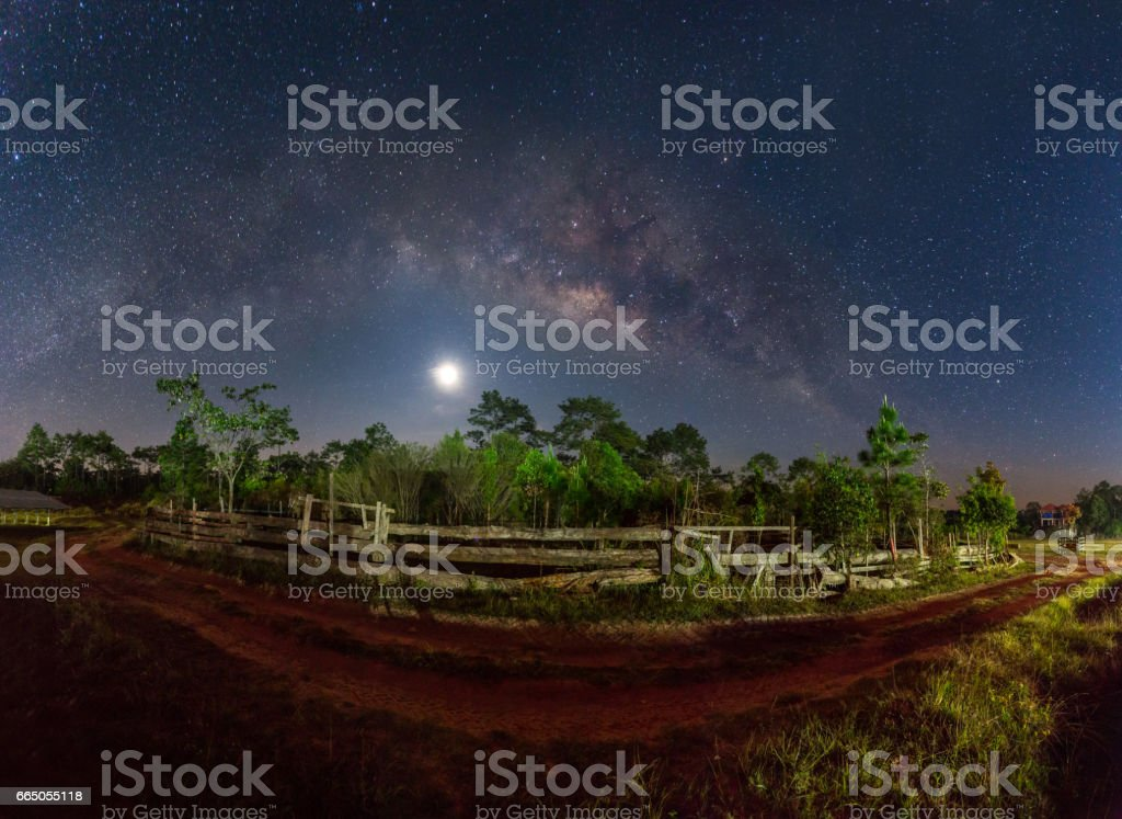 milky way and fullmoon over dirt road in country side stock photo