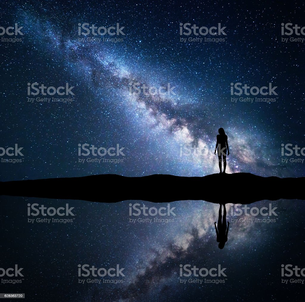 Milky Way and silhouette of a standing woman on mountain stock photo