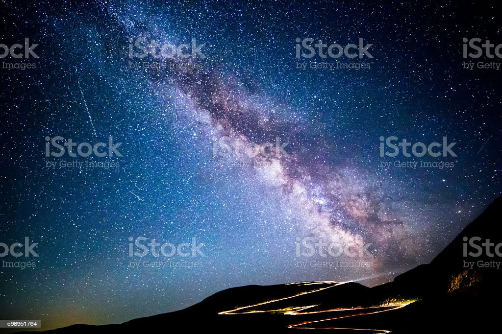 Milky way and traffic trails on Transalpina pass stock photo