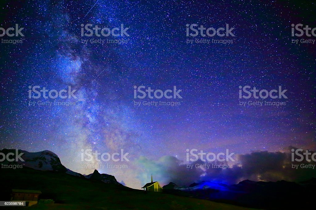 Milky Way galaxy above chapel, Swiss Alps landscape at night stock photo