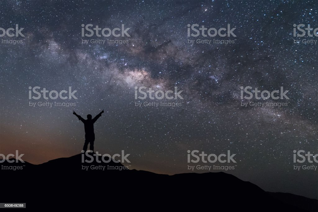 Milky Way landscape. Man standing on top mountain with night sky stock photo