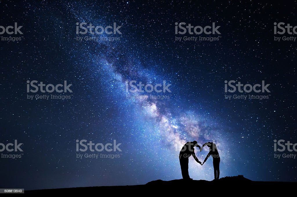 Milky Way. Man and woman holding hands in heart shape stock photo