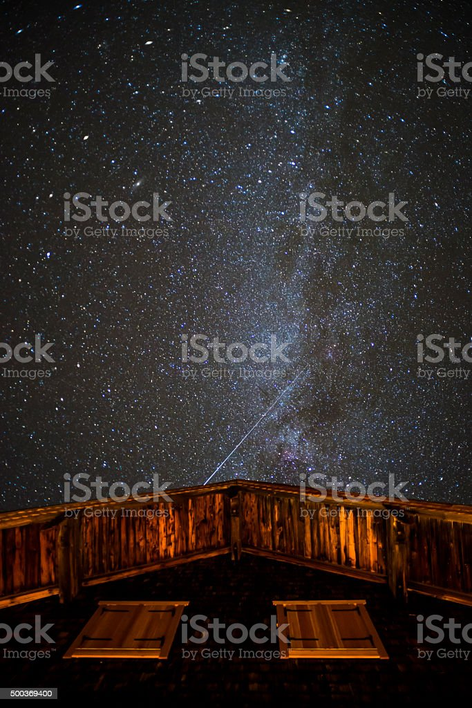 Milky way, meteorite spur and stars over mountain hut stock photo