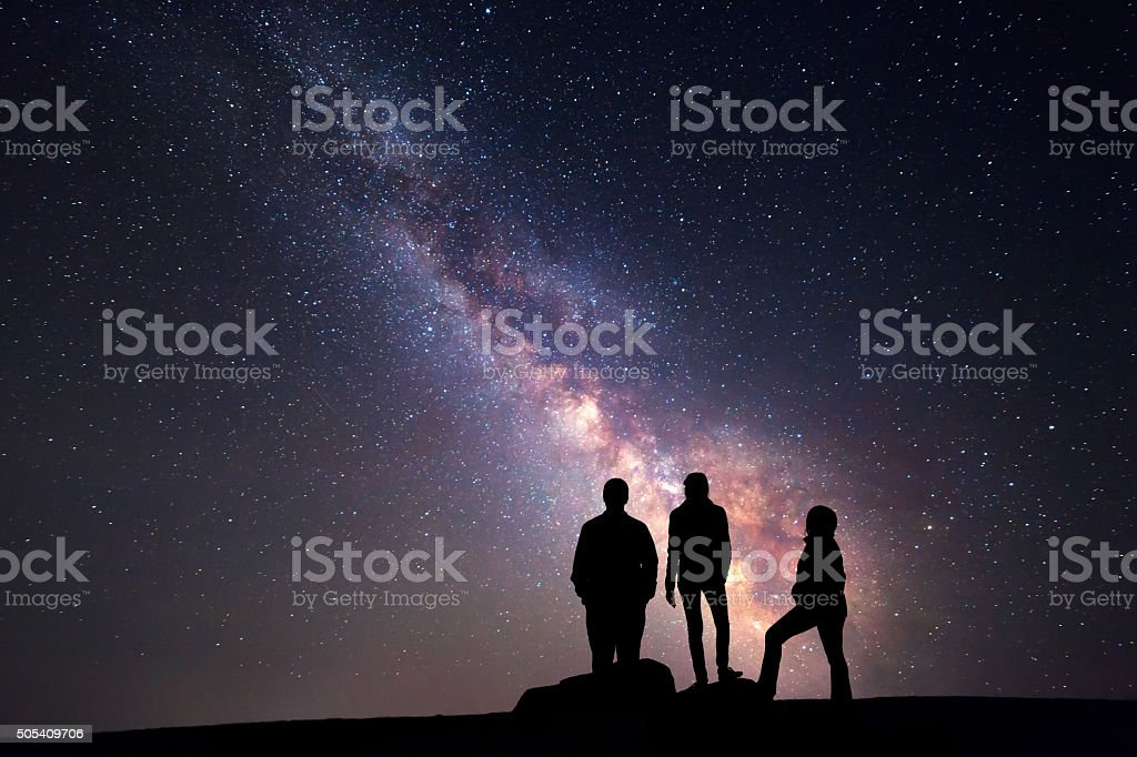 Milky Way. Night sky and silhouette of a family stock photo