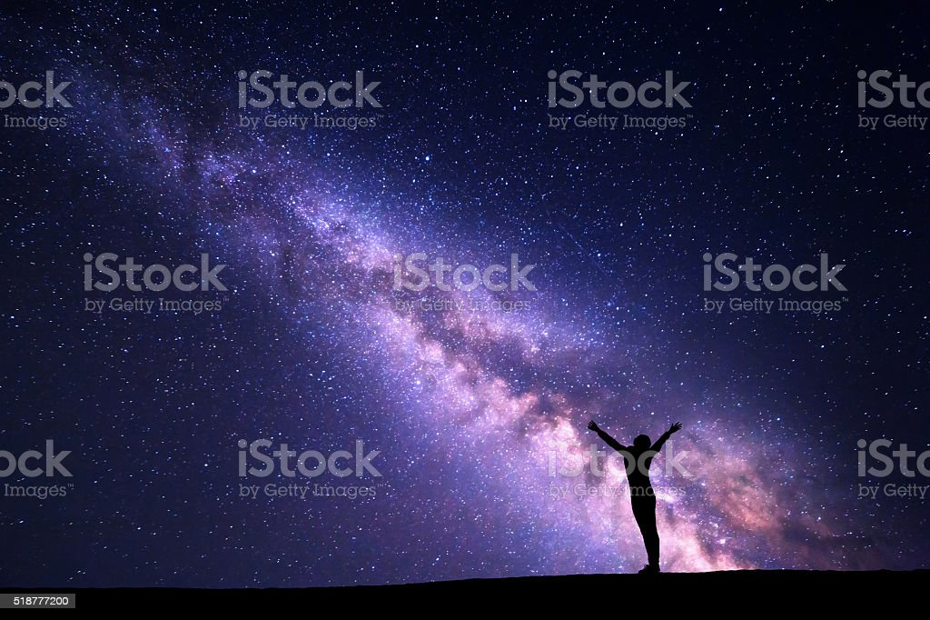 Milky Way. Night sky and silhouette of a happy girl stock photo