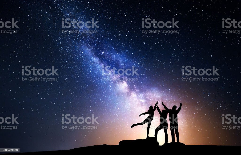 Milky Way. Night sky with silhouette of a happy family stock photo