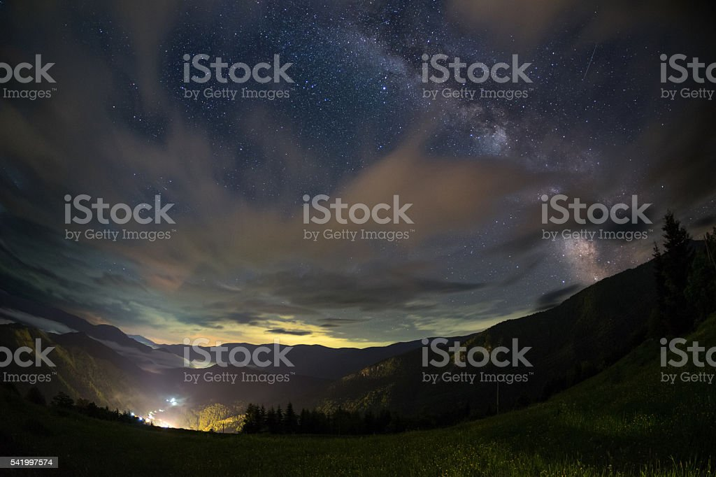 Milky way over a mountain valley and village stock photo