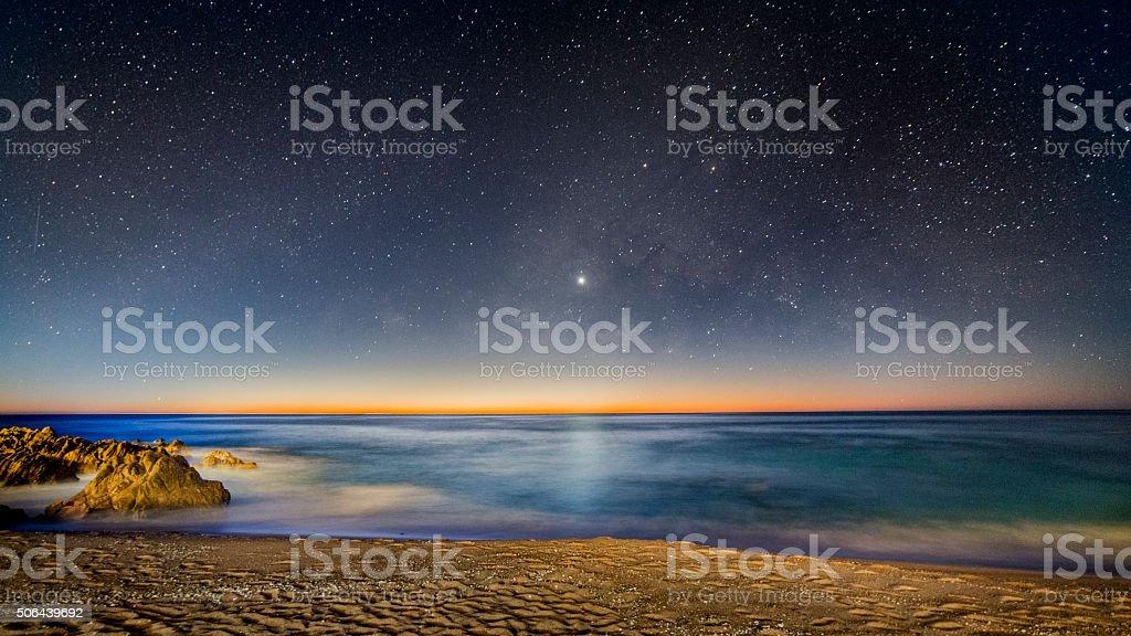 Milky Way Over Sunrise over Ocean stock photo