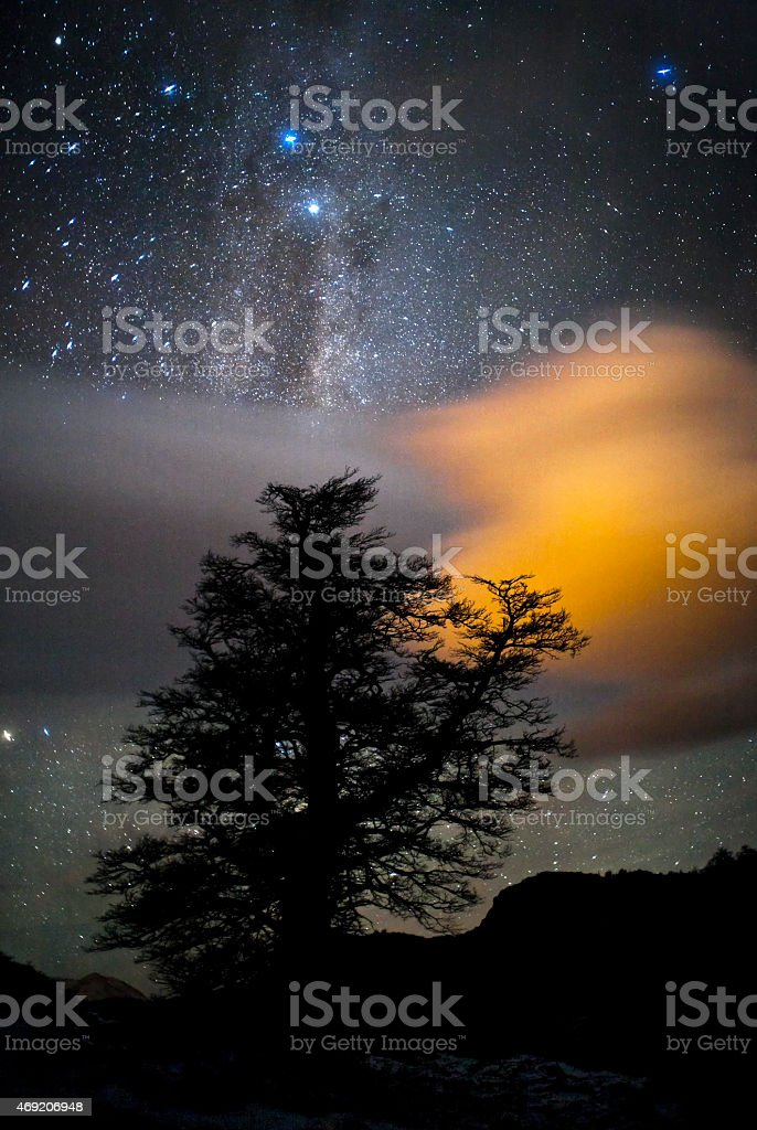 Milky way, tree, and clouds stock photo