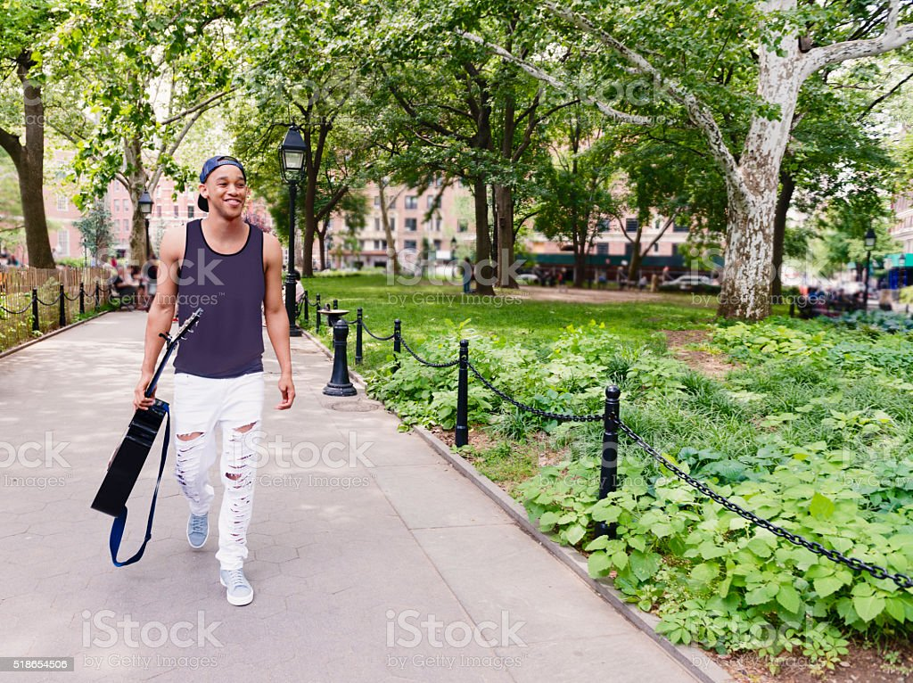 Millennial Black Man Walks with Acoustic Guitar in NYC Park stock photo