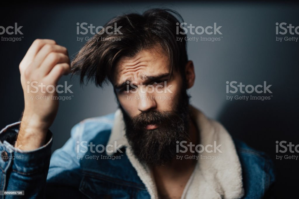Millennial man running hands through hair stock photo