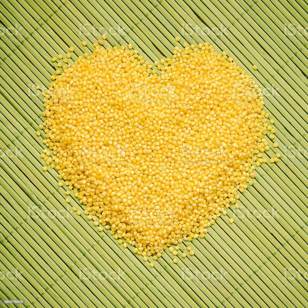 Millet groats heart shaped on green mat surface. stock photo