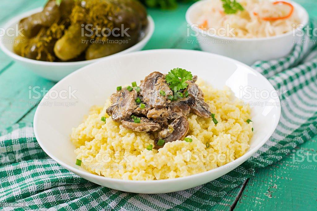Millet porridge with mushrooms in a white bowl stock photo