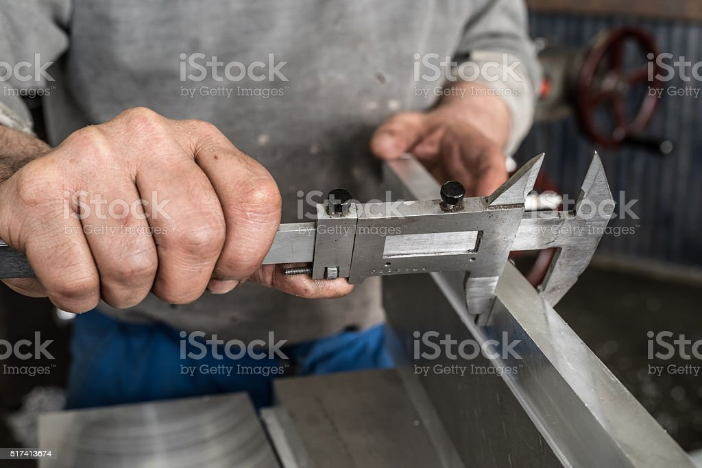 Milling machine checks the thickness of the metal piece stock photo