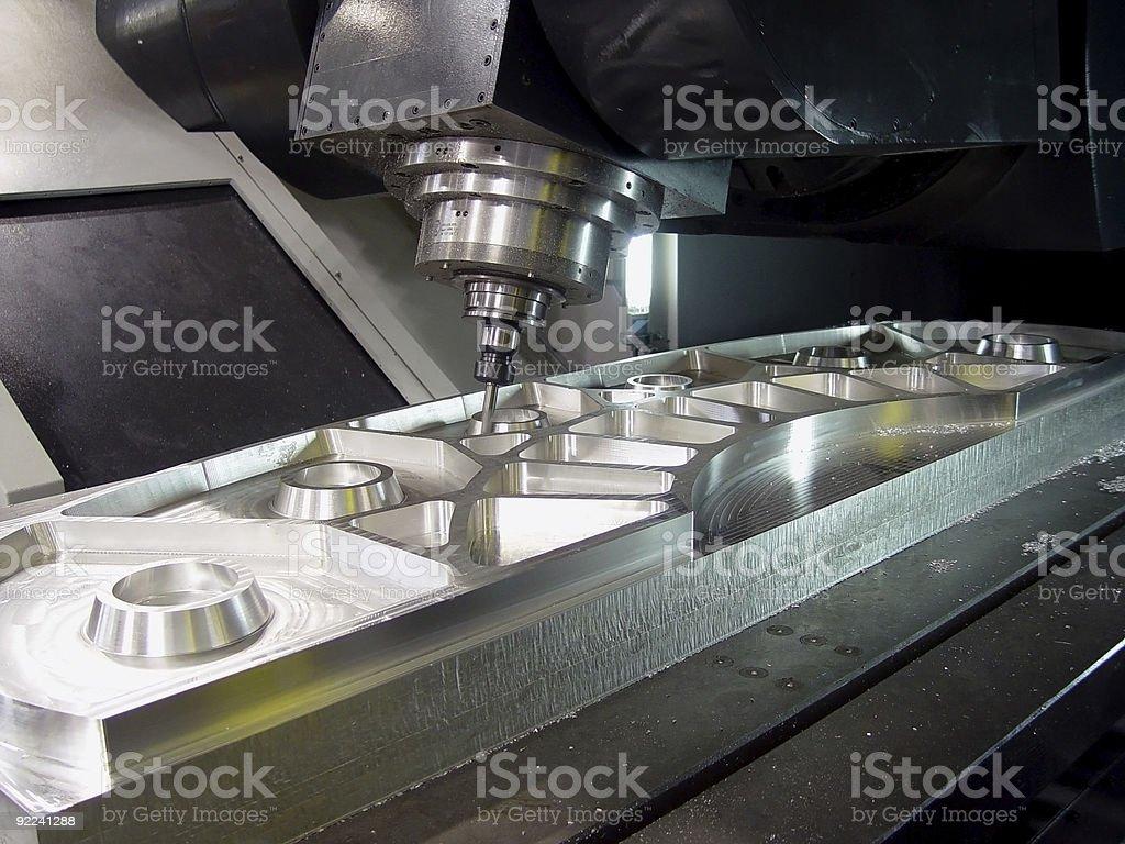 A milling machine cuts aluminum parts stock photo
