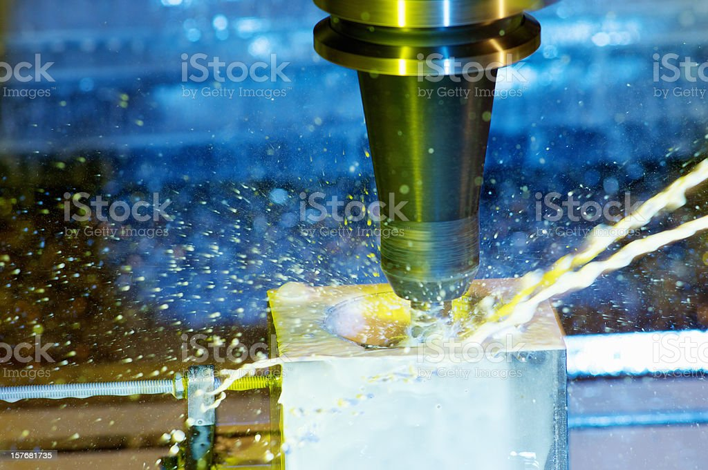 CNC milling machine cutting into steel stock photo