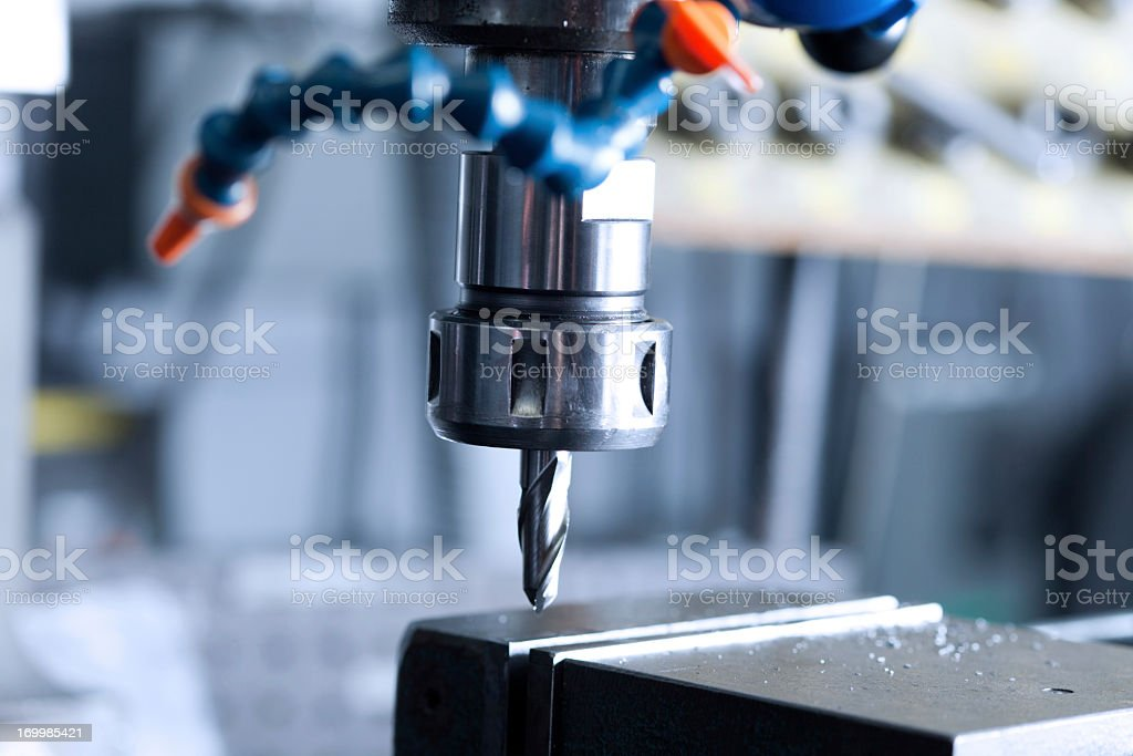 Milling machine drilling ditch on a piece of metal stock photo