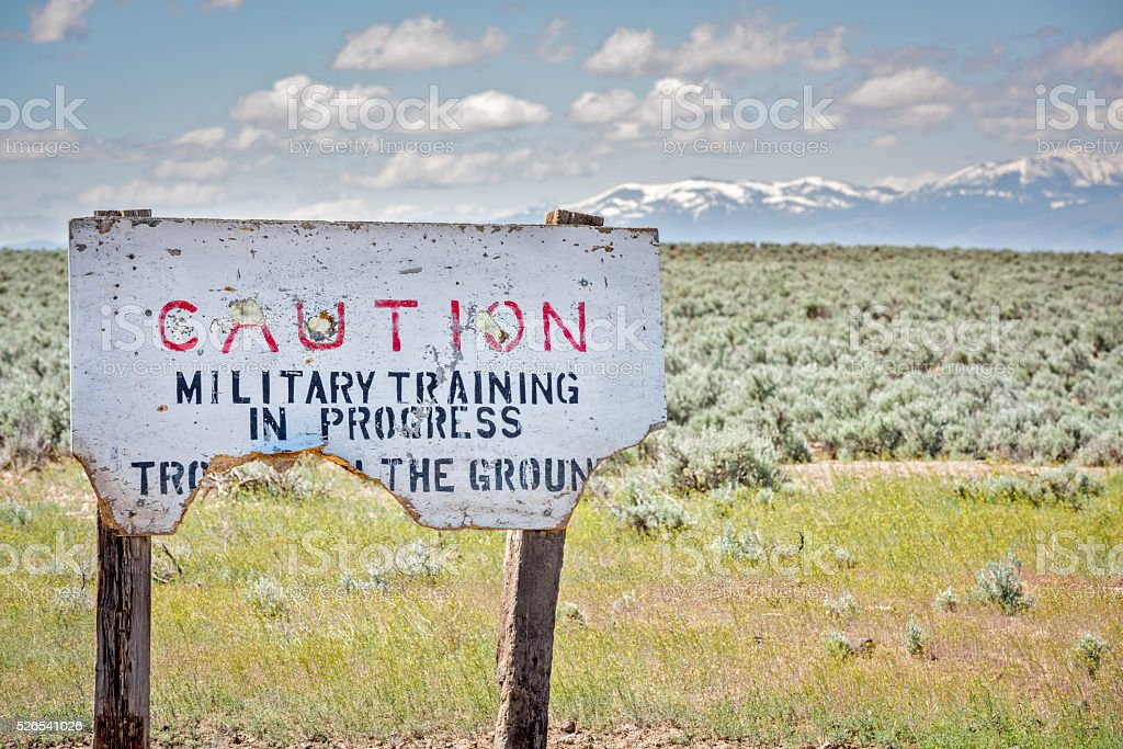 Millitary training area warning sign that is shot up stock photo