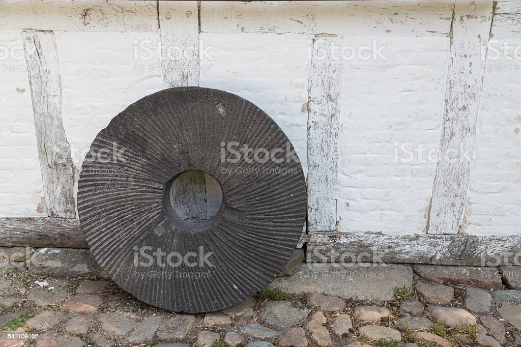 Millstone standing on a wall stock photo