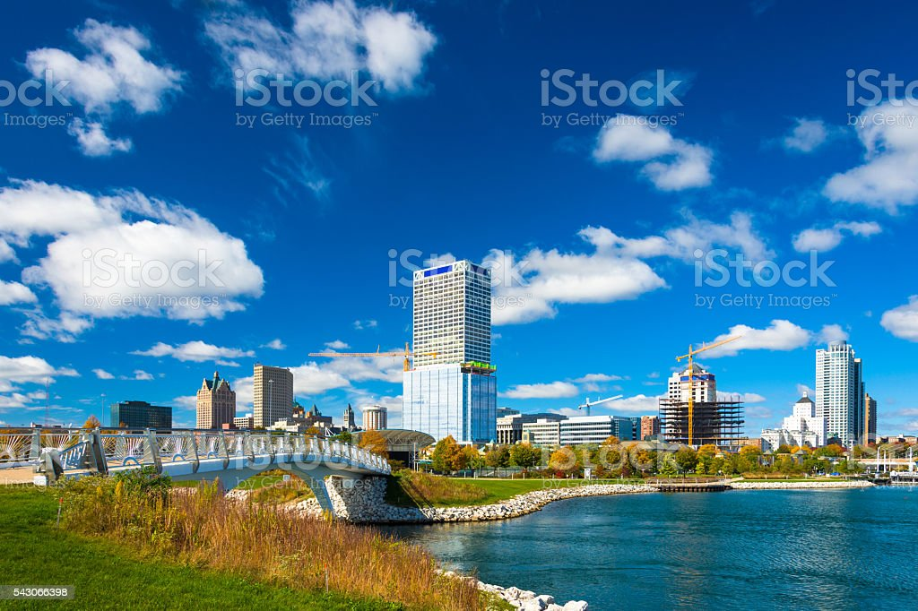 Milwaukee Skyline with Dramatic Clouds, Park, Bridge, and Inlet stock photo