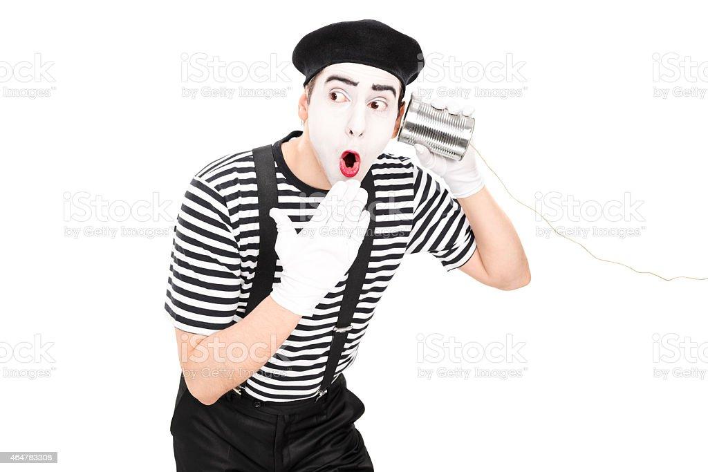 Mime artist listening through a tin can phone stock photo