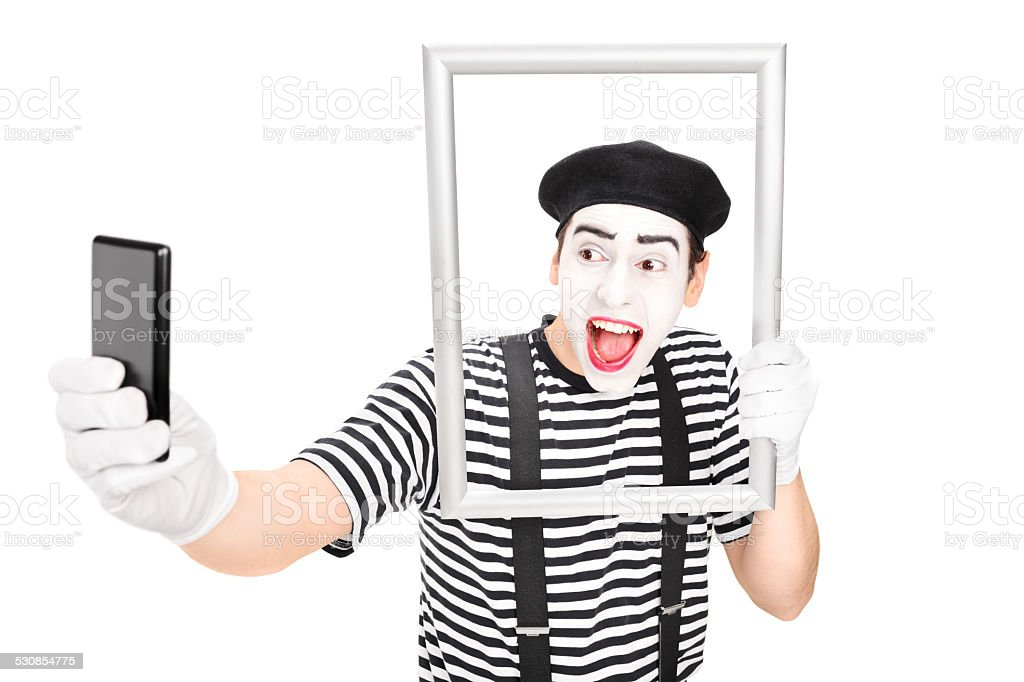 Mime artist taking selfie behind a picture frame stock photo