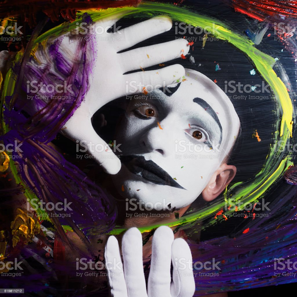 Mime behind glass with multi-colored stains stock photo