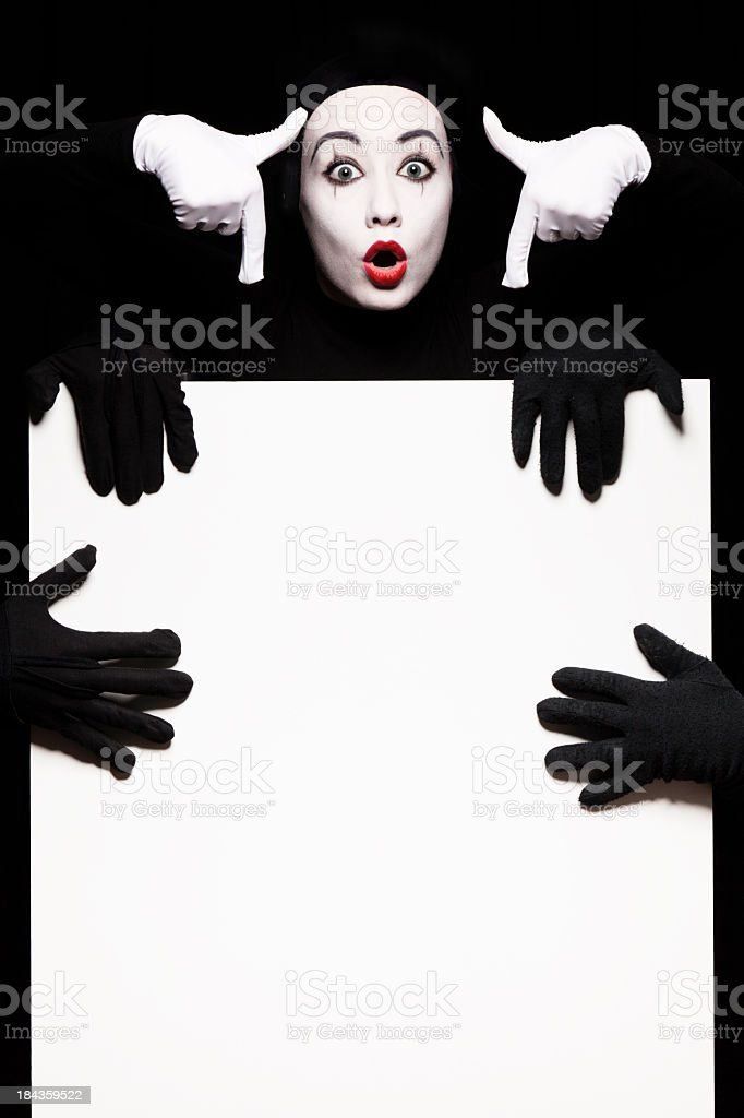Mime pointing down at four extra hands holding white poster royalty-free stock photo