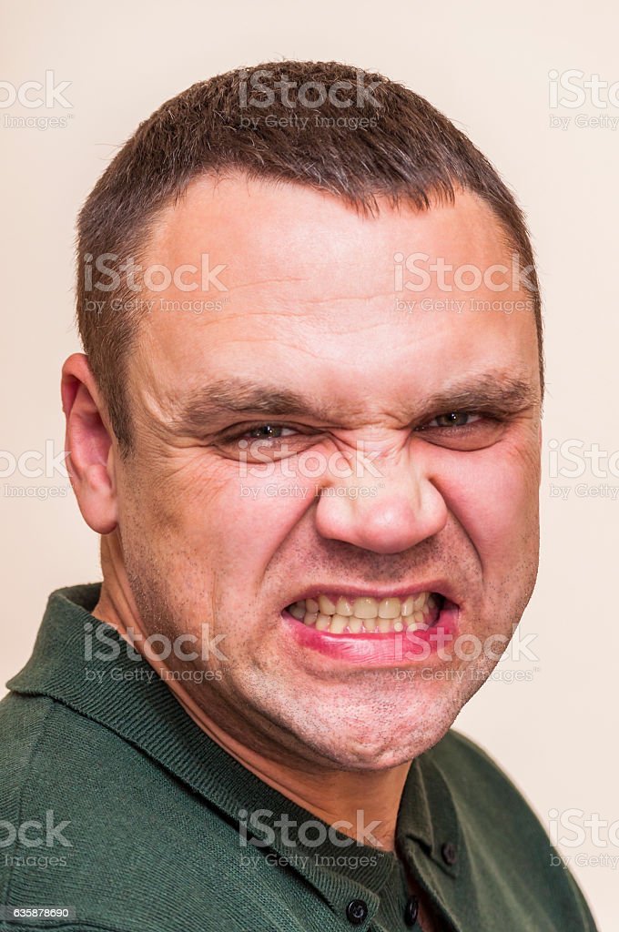 Mimicry of depressed, angry, grining man on white background stock photo