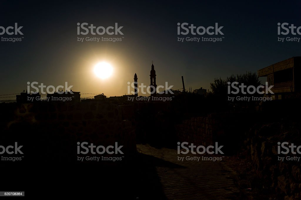 minaret and church tower silhouette in midyat mardin turkey stock photo