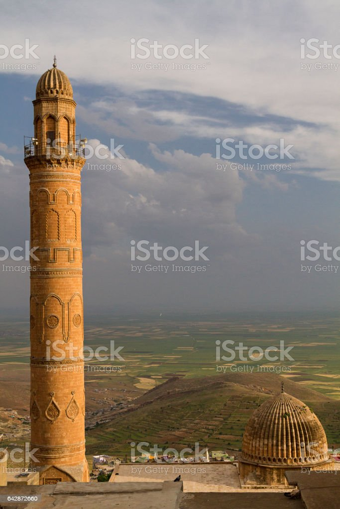 Minaret of the Great Mosque known also as Ulu cami in Mardin, Turkey. Mesopotamian plain is shown in the background. It is located very close to the border between Turkey and Syria. stock photo