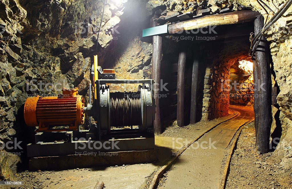 Mine tunnel with mechanical winch, rail track and pit props royalty-free stock photo