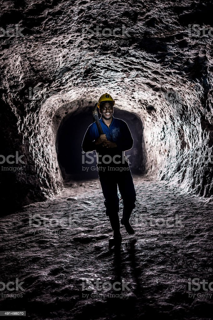 Miner inside a dark tunnel at a mine stock photo