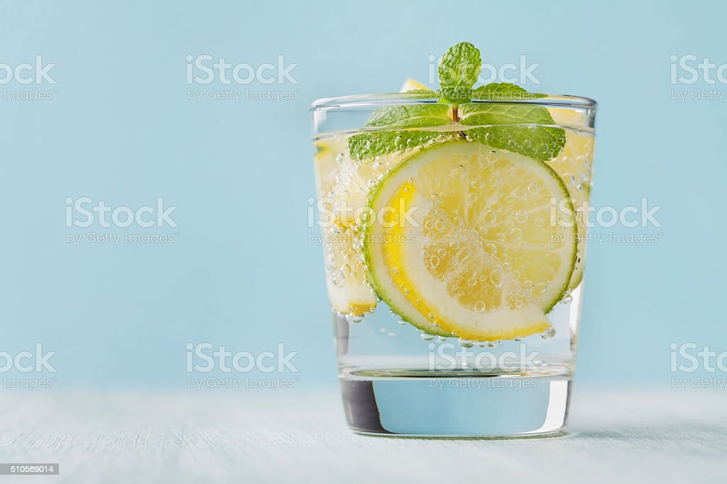 Mineral infused water with limes, lemons, ice and mint leaves stock photo
