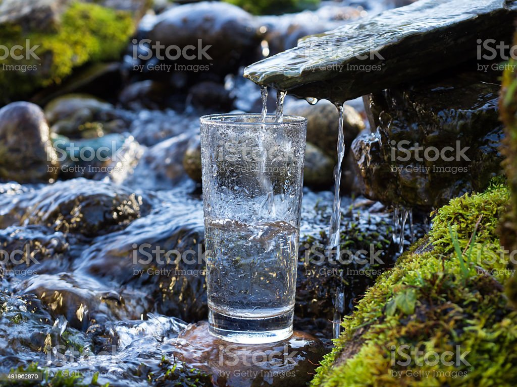 Mineral water is being poured into glass stock photo