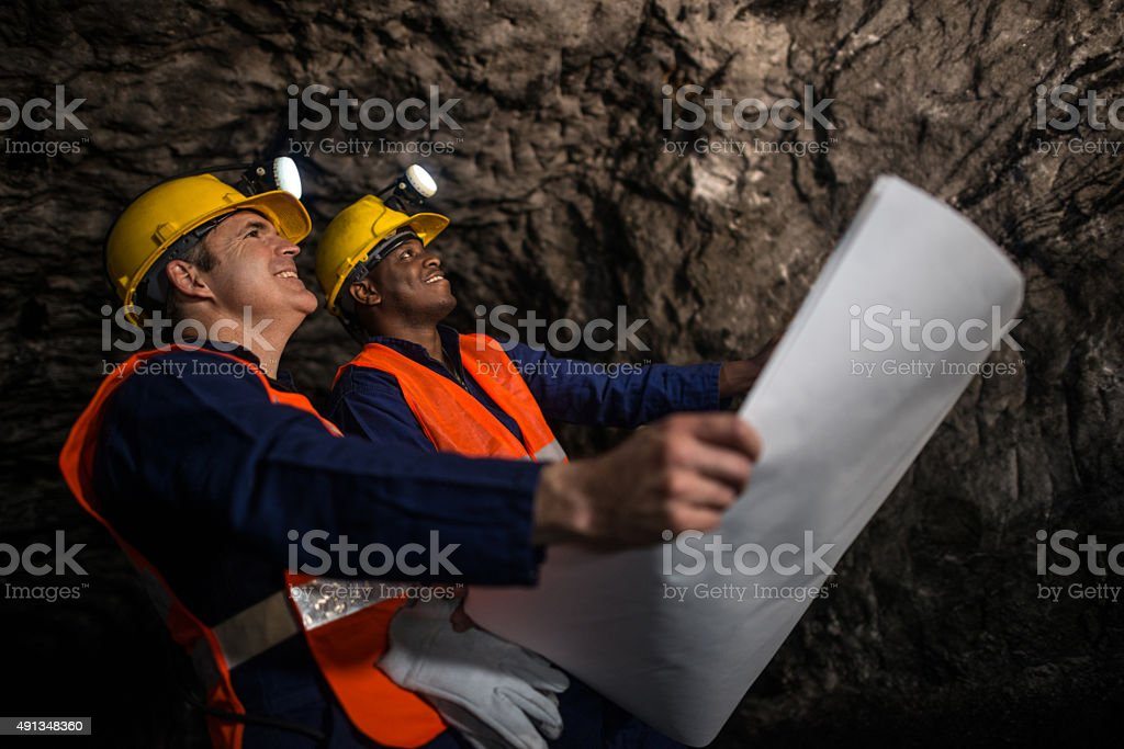 Miners working at the mine holding a blueprint stock photo