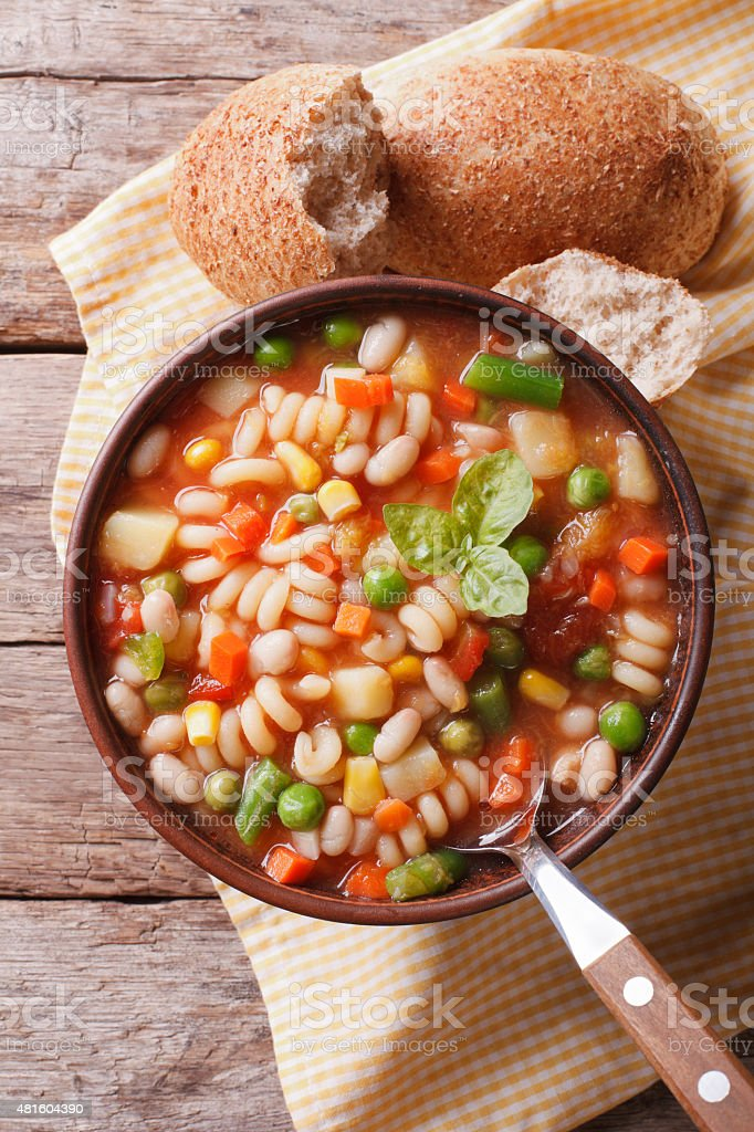 minestrone soup and bread on the table. Vertical top view stock photo