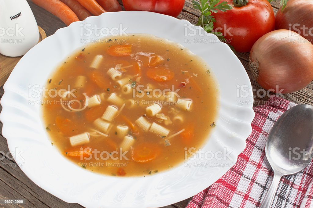 Minestrone soup in plate on wooden table stock photo