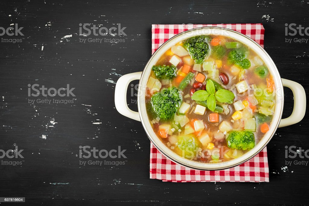Minestrone soup on the dark background. Rustic style stock photo