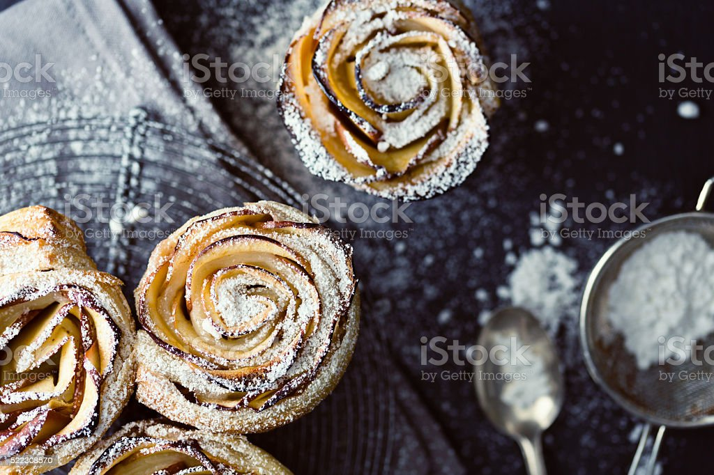 mini apple roses puff pastry with icing sugar. stock photo