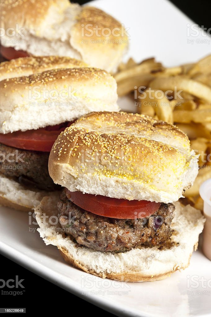 Mini beef burgers served with fries on a white plate stock photo