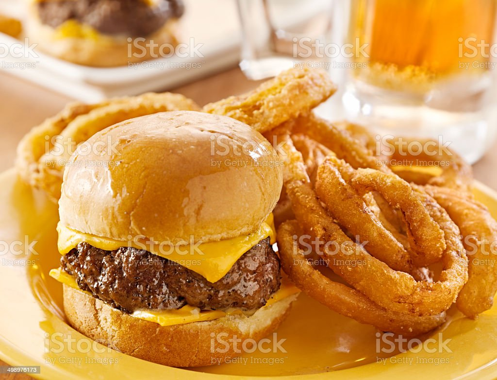 mini burgers with cheese and onion rings served with beer. stock photo