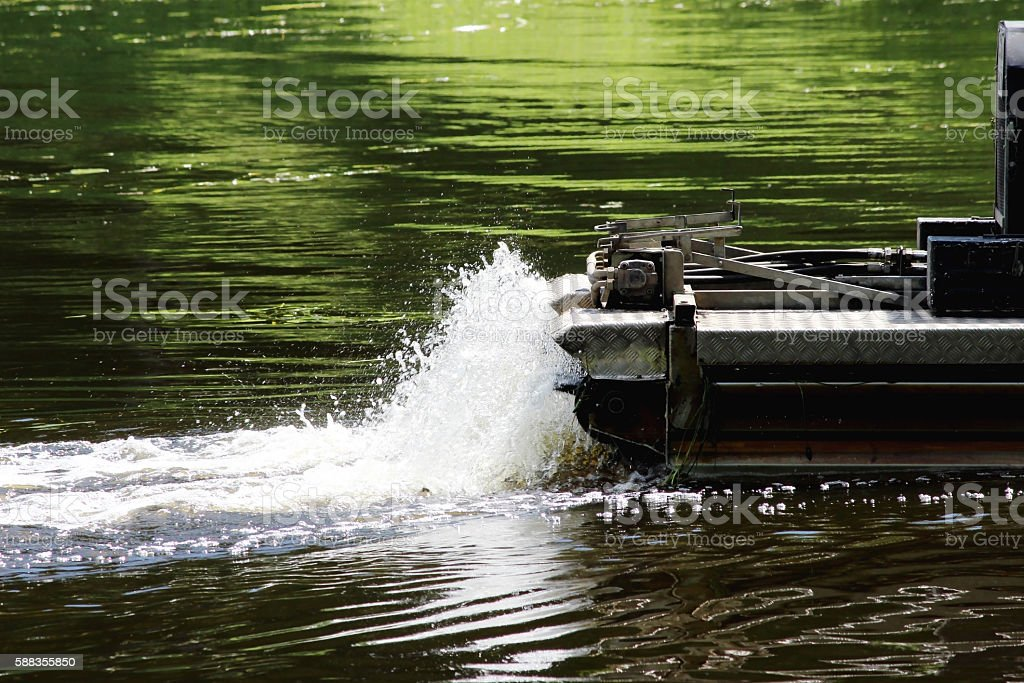 mini dredger is clearing lake algae summer day. stock photo