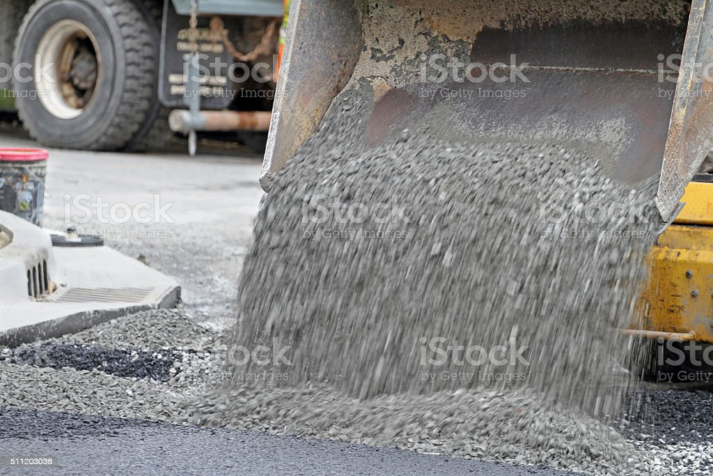 Mini Front End Loader Dumping Gravel On Road Repair Site stock photo